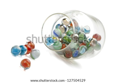 Close-up image of a transparent jar with colorful marbles over the white background - stock photo