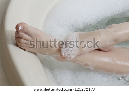 Close-up image of a woman leg soaked in spume - stock photo