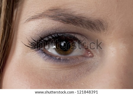 Close-up image of a woman's eye with eye shadow looking at the camera