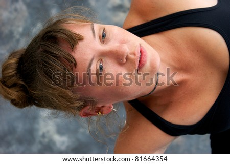 Close up image of a woman's face as she exercises and her head is sideways. - stock photo
