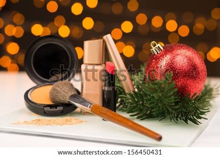Close-up image of a X-mas ball and cosmetics for the New Year celebration on the foreground - stock photo