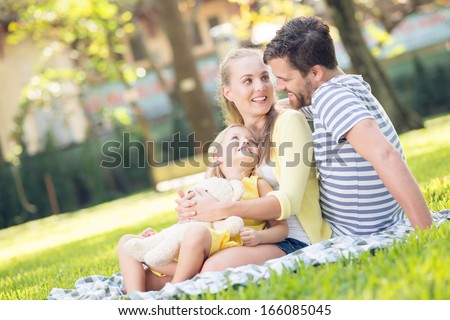 Close-up image of a young cheerful family resting in the park - stock photo