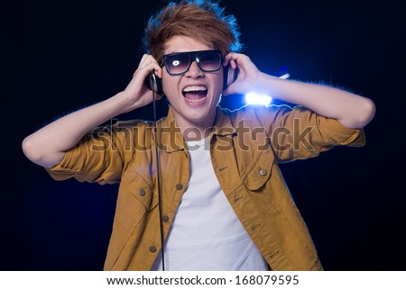 Close up image of a young excited DJ with headphones in the night club  - stock photo
