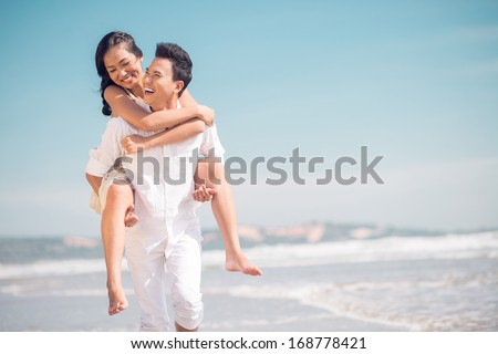 Close up image of a young funny couple piggybacking on the beach  - stock photo