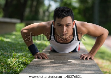 Close-up image of a young sportsman doing push-ups outside - stock photo