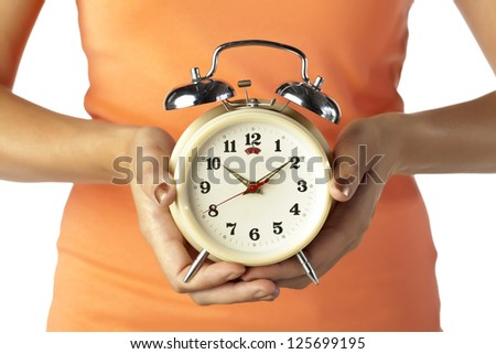Close up image of alarm clock in human hand against white background - stock photo