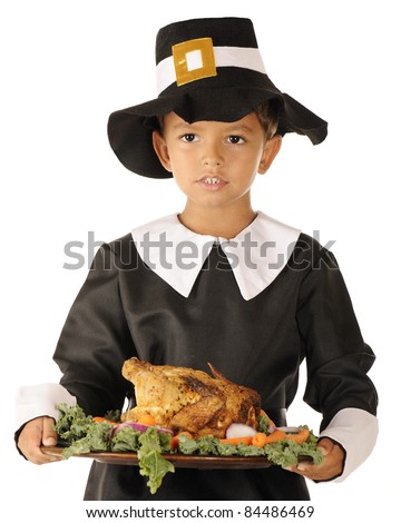 Close-up image of an adorable preschool boy in Pilgrim clothes holding a wooden platter with roast foul surrounded by colorful vegetables.  On a white background. - stock photo