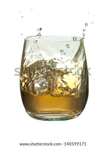 Close-up image of an ice cube splashed into the glass of brandy against the white background