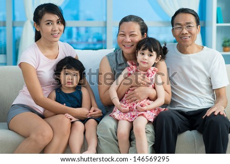 Close-up image of an mixed-race family smiling and looking at camera - stock photo