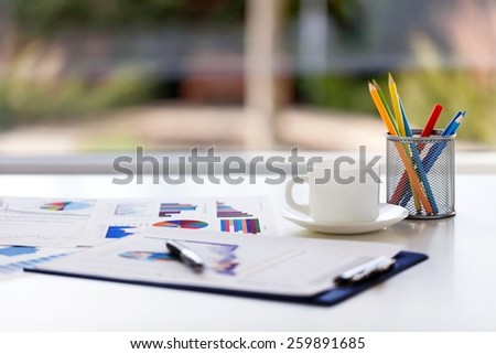 Close-up image of an office desk at morning with a cup of tea and financial documents - stock photo