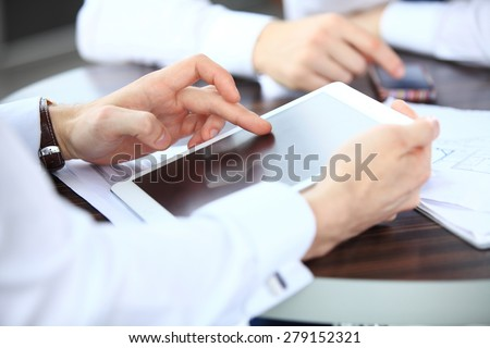 Close-up image of an office worker using a touchpad to analyze statistical data