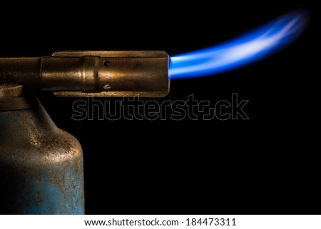 Close up Image of an Old Gas Burner with Flame Isolated on a Black Background - stock photo