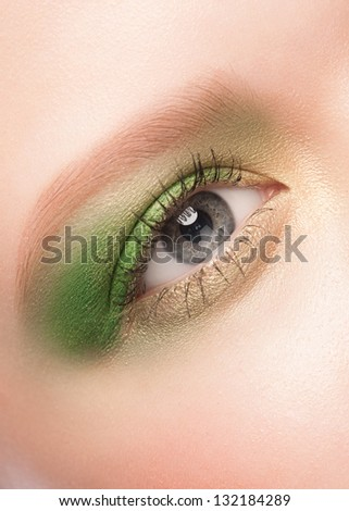 Close-up image of beautiful woman blue eye with bright green makeup