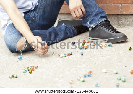 Close-up image of boy's hand playing marbles on the street - stock photo