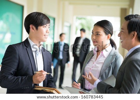 Close-up image of business colleagues explaining the strategy on the foreground - stock photo