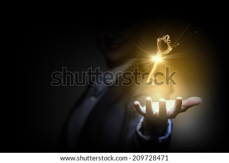 Close up image of business person holding shining key - stock photo