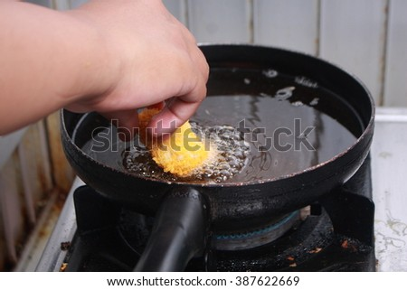 Close up image of chef hand putting chicken nuggets tempura in to hot oil pan for deep fry cooking - stock photo