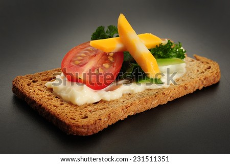 Close-up image of crackers with some cream tomato and cheese - stock photo