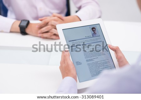 Close-up image of employer reading cv of job candidate - stock photo