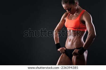 Close up image of  female in sports clothing relaxing after workout on dark background. Muscular female body with sweat. Image with copyspace for text - stock photo