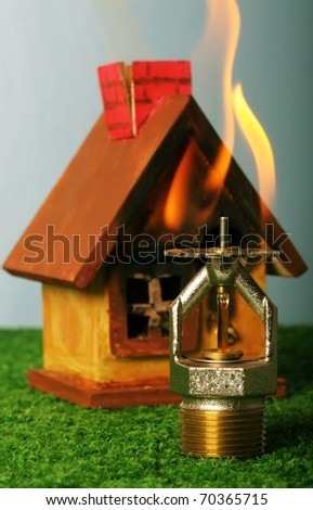 Close up image of fire sprinkler. Fire sprinklers are part of an integrated water piping system designed for life and fire safety. Replica of house on fire added to background. - stock photo