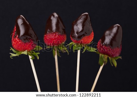 Close up image of four strawberries with melted chocolate on dark background - stock photo
