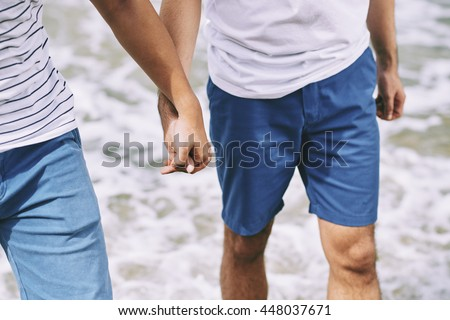 Close-up image of gay couple holding hands when walking on the beach - stock photo