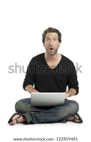 Close up image of good looking guy shocked while using laptop against white background