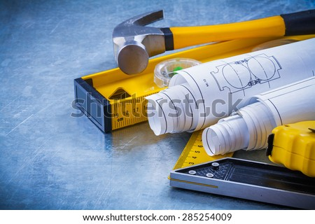 Close up image of hammer measuring line construction plans and level square ruler on metallic background maintenance concept. - stock photo