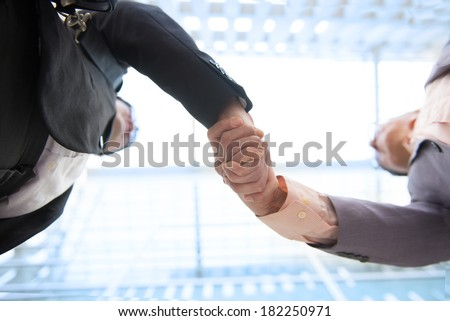 Close up image of hand shake against skyscrapers, low angle  - stock photo