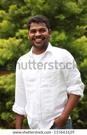 Close-up image of healthy, relaxed & happy asian/indian executive with positive expression. The person is wearing a white shirt & the picture is shot in natural settings - stock photo