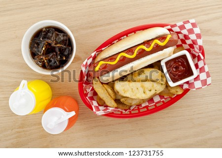 Close up image of hot dog sandwich with fried potato fries with drinks on wooden table - stock photo