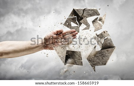 Close up image of human hand breaking recycle stone symbol