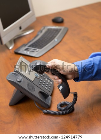 Close-up image of human hand disconnecting land line phone on wooden office desk with desktop computer in background. - stock photo