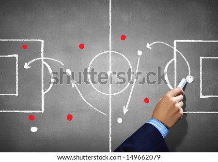Close up image of human hand drawing football tactic plan - stock photo