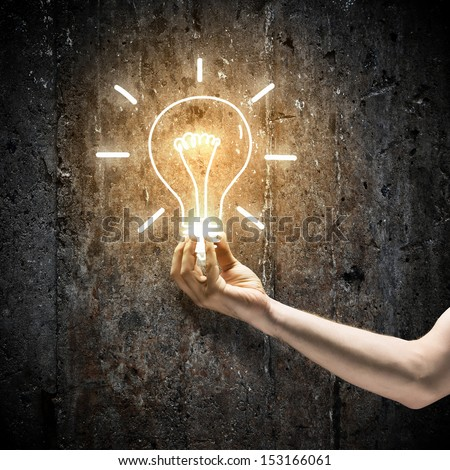 Close up image of human hand holding electrical bulb in darkness - stock photo