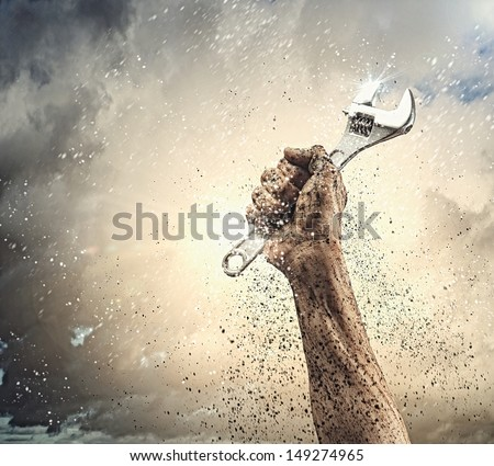 Close-up image of human hand holding wrench. Construction - stock photo