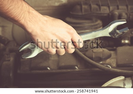 Close-up image of human hand holding wrench over car chassis