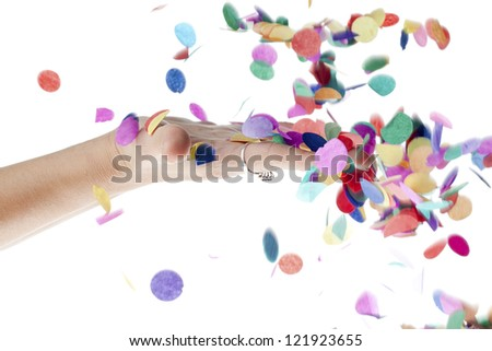 Close-up image of human hand touching decorative confetti falling against white background. - stock photo