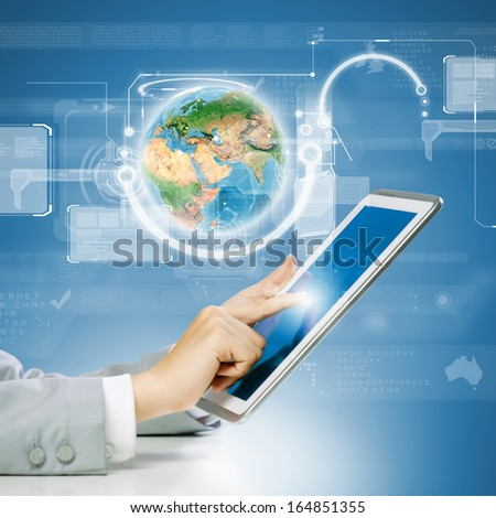 Close up image of human hand touching screen of tablet pc. Elements of this image are furnished by NASA