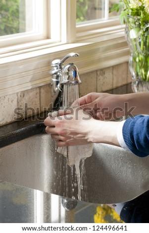 Close up image of human hand washing dish cloth - stock photo