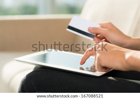 Close-up image of human hands holding credit card while touching a tablet for the Internet payment on the foreground  - stock photo