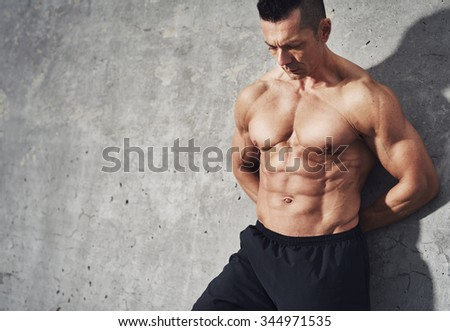 Close up image of male in shorts relaxing after workout on grey background. Muscular male body with sweat. Image with copyspace for text