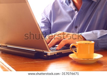 close up image of man using laptop next to cup of coffee. retro style image. selective focus
