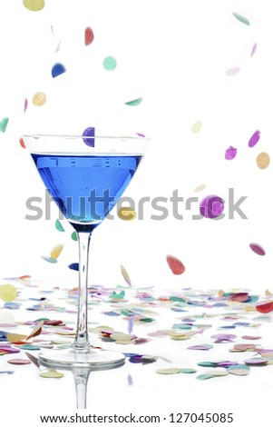 Close-up image of martini glass with curacao and colorful confetti falling on white background. - stock photo