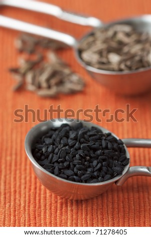 Close up image of measuring spoons with black cumin seeds and orange background. - stock photo