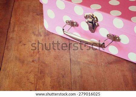 close up image of pink suitcase with polka dots over wooden table - stock photo