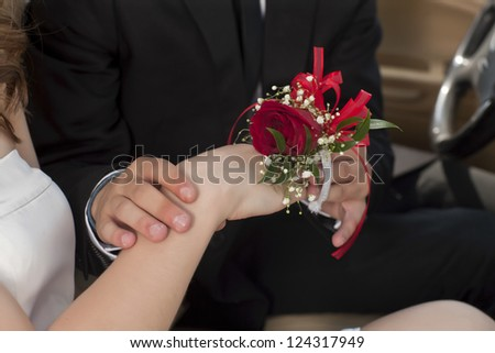 Close up image of placing a red rose corsage in a woman wrist
