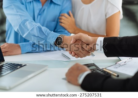 Close-up image of real estate agent and his client shaking hands - stock photo