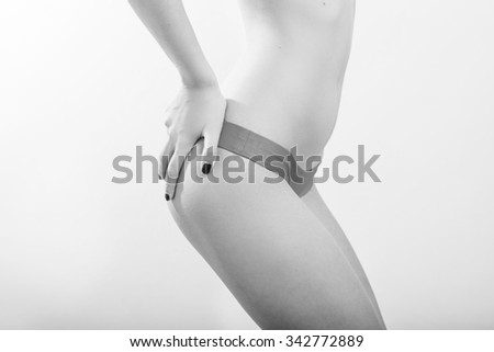 close up image of sexy girl showing her perfect fitness shape with hands on buttocks in lingerie posing on light copyspace background. Black and white photography - stock photo